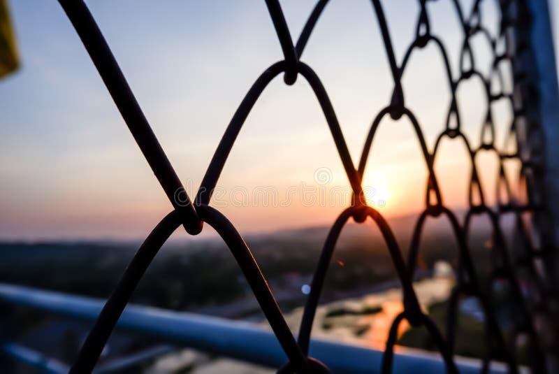 Staketskyddsgallrar med solnedgångsuddighetsbakgrund royaltyfria foton
