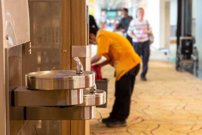 Stal nierdzewna pije fontanny w lotnisku Mężczyzny napoju woda na tle obraz royalty free