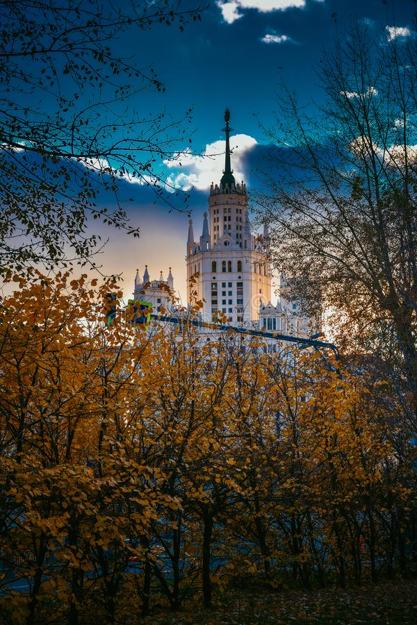 Stalinist skyscraper through the autumn trees at sunset royalty free stock photos