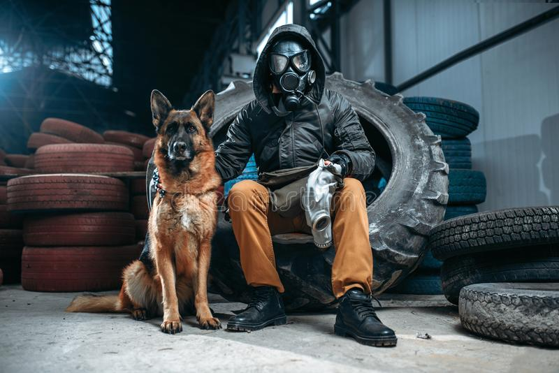 Stalker in gas mask and dog, post-apocalypse. Stalker in gas mask and dog, friends in post apocalyptic world. Post-apocalypse lifestyle on ruins, doomsday stock image