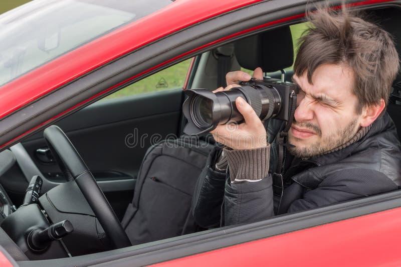 Stalker of paparazzi nemen foto met camera van auto royalty-vrije stock afbeeldingen