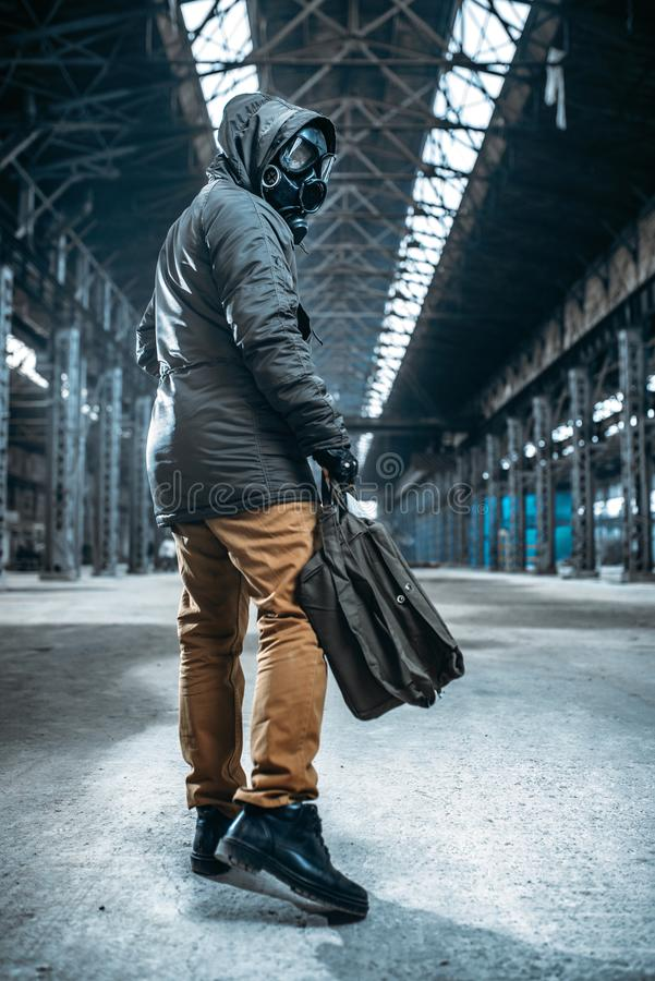 Stalker soldier in gas mask, horror of nuclear war. Stalker soldier, man in gas mask in abandoned building. Post apocalyptic lifestyle, doomsday, horror of royalty free stock images