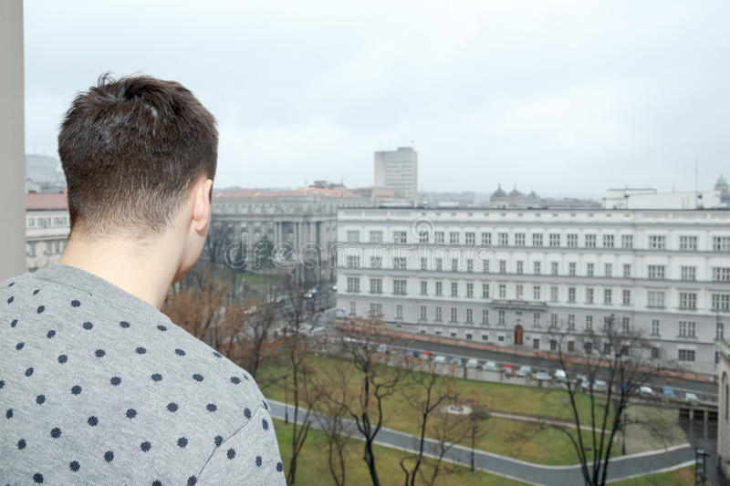 Stalker watching someone. Young man at balcony in depression suffering emotional crisis. Attractive male model looking down from balcony. Person on terrace looks royalty free stock image