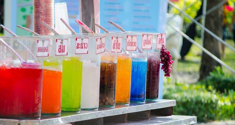 Stall för drink för fruktfruktsaft i variation av anstrykningar i slut upp med namn för thailändskt språk av drinketiketter arkivbild