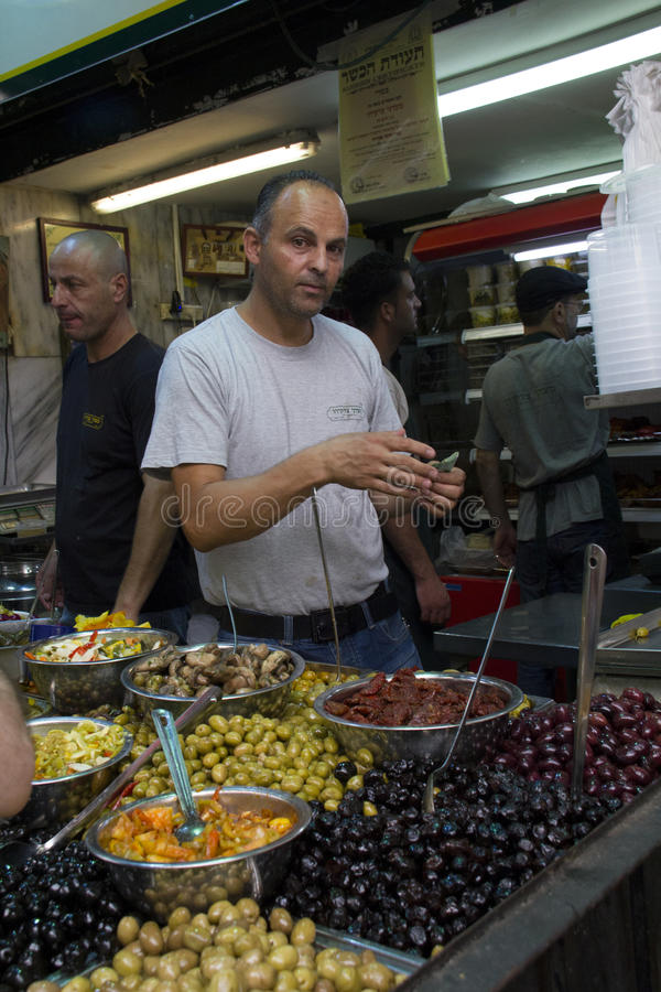 A stall holder serves customers at the famous Market Mahane Yeh. Jerusalem,Israel - JULY 30, 2013:A stall holder serves customers at the Jerusalem Market in royalty free stock photos
