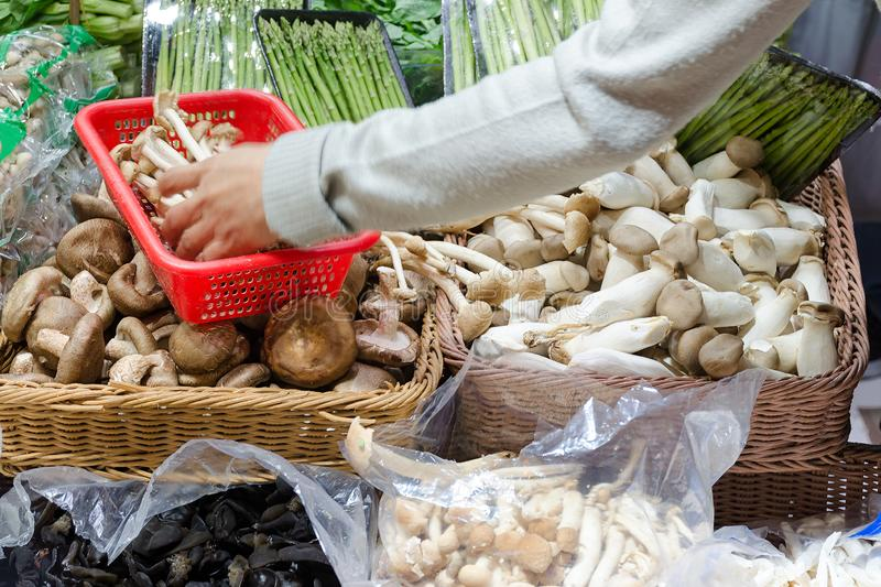 Stall with mushrooms and asparagus sprouts, hand fills the basket with mushrooms. Photo with blur in motion. Hong Kong, China royalty free stock photos