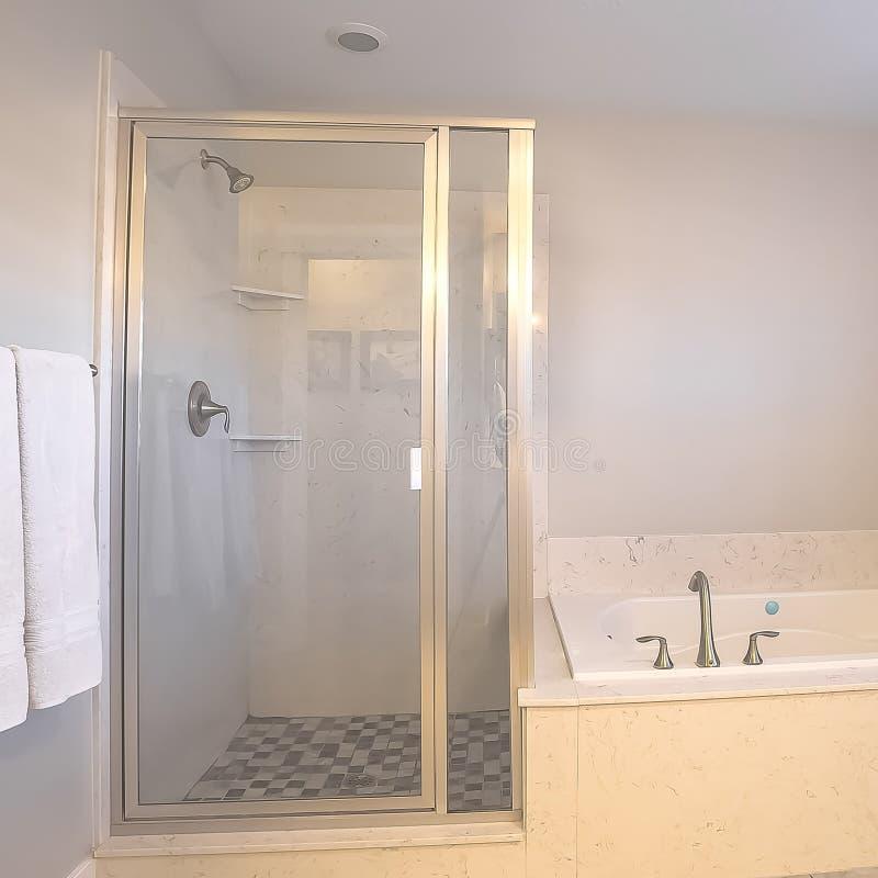 Stalle de douche carrée de cadre et construit dans la baignoire à l'intérieur d'une salle de bains avec le mur gris-clair image libre de droits