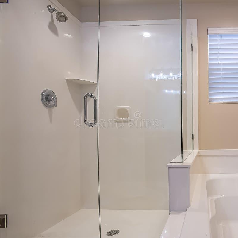 Stalle de douche murée par verre carrée de cadre et baignoire brillante à l'intérieur de la salle de bains d'une maison photos stock