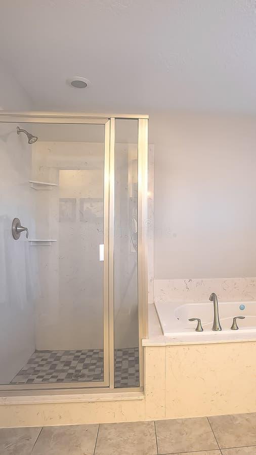 Stalle de douche verticale de cadre et construit dans la baignoire à l'intérieur d'une salle de bains avec le mur gris-clair images libres de droits