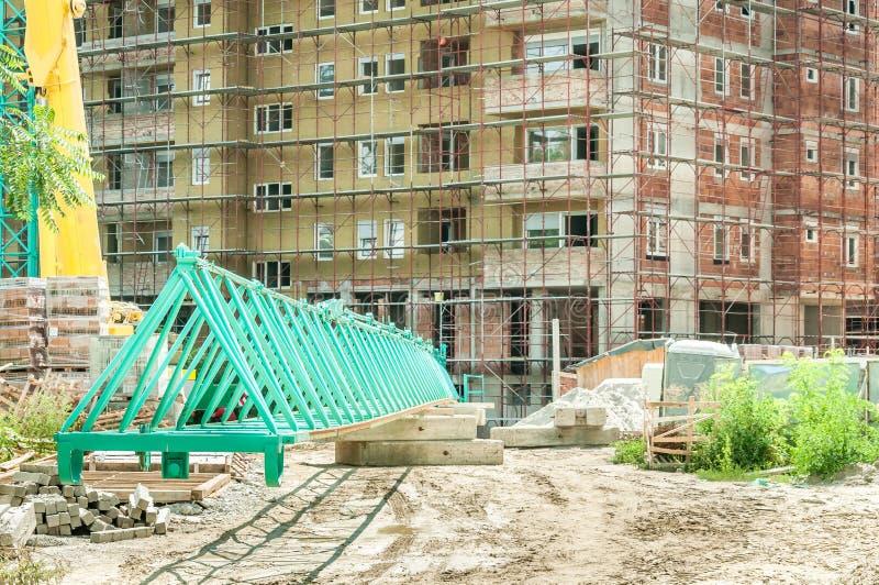 Stalowa część żuraw na budowie z budynkiem i rusztowaniem w tle, selekcyjna ostrość obrazy stock