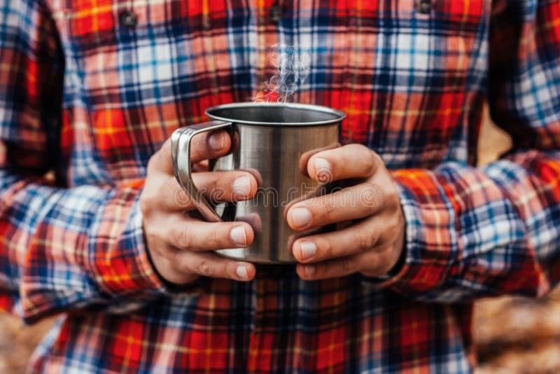Stalowa filiżanka z gorącym napojem w mężczyzna rękach w jesień parku fotografia royalty free