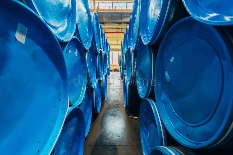 Stalowe drymby zakrywać z błękitnymi nakrętkami w magazynie obrazy stock