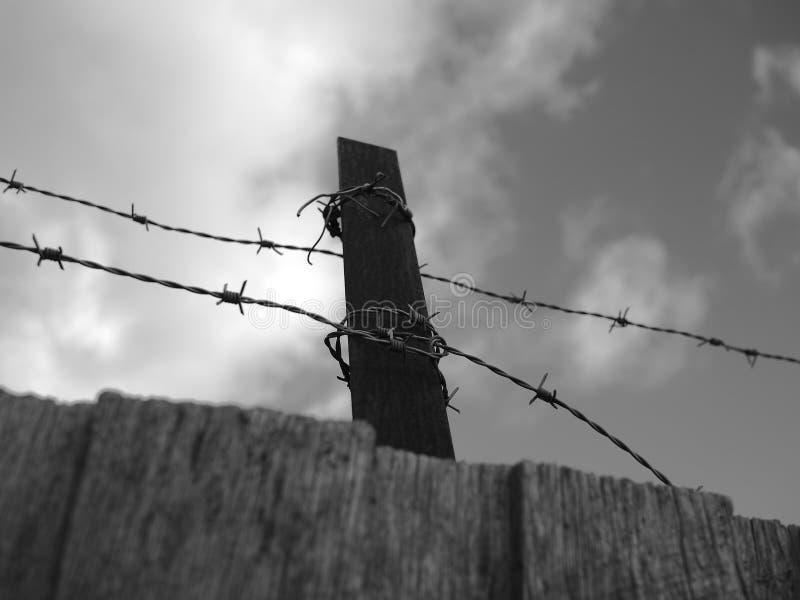 Stalowy barbeta drut na ogrodzeniu pod chmurnym niebem czarny i biały zdjęcie stock
