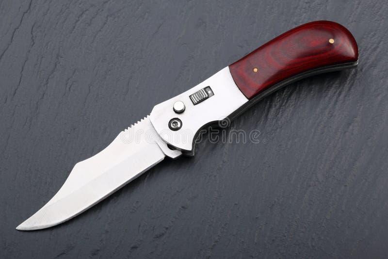 Stalowy falcowanie nóż z otwartym ostrzem drewnianą rękojeścią na kamiennej powierzchni i Stali ręki Pojęcie broń, polowanie lub  zdjęcia stock