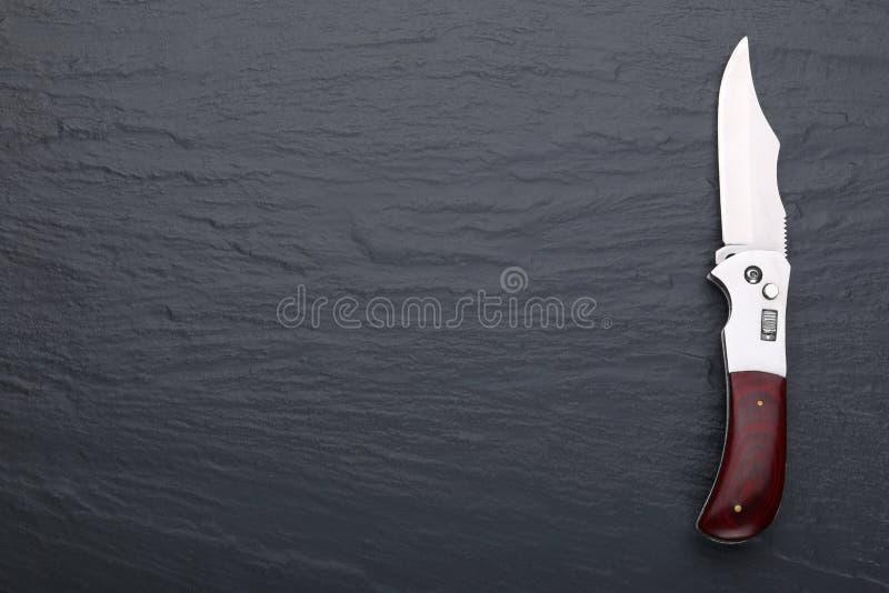 Stalowy falcowanie nóż z otwartym ostrzem drewnianą rękojeścią na kamiennej powierzchni i Stali ręki Pojęcie broń, polowanie lub  fotografia royalty free