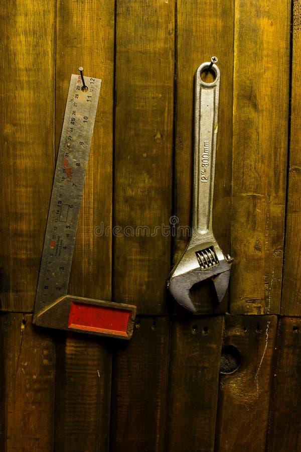 Stalowy otokowy setsquare i wyrwania obwieszenie na drewnianej ?cianie zdjęcie stock