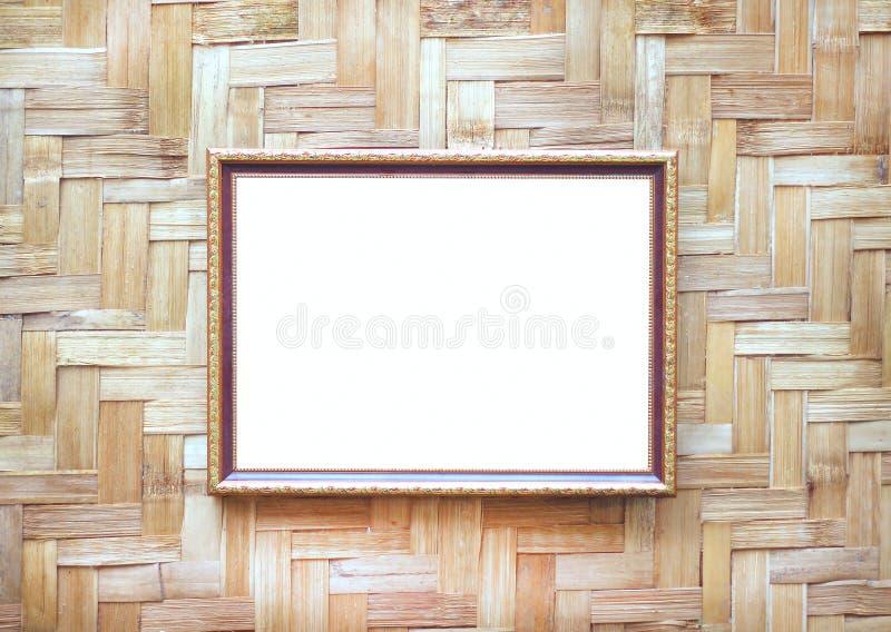 Stalowy złocisty obrazek ramy dekoracyjny obwieszenie na drewno wyplatającym ściennym tle zdjęcie royalty free