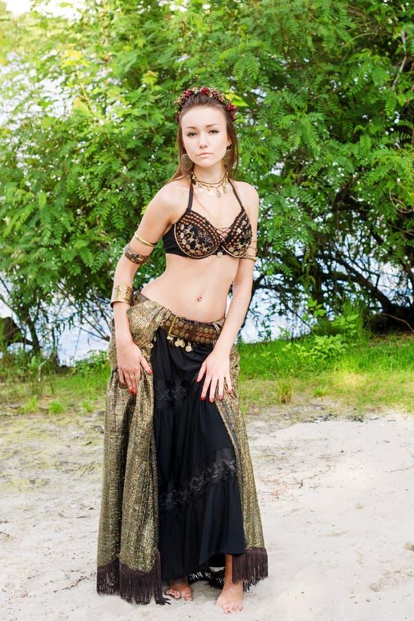 Stam- amerikansk stildansare för ung kvinna Flickadans och posera på dräkten för magdans för strandsand den bärande ethnic fotografering för bildbyråer