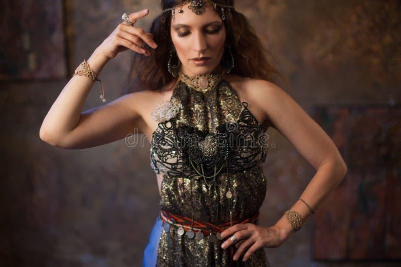 Stam- dansare, härlig kvinna i den etniska stilen på en texturerad bakgrund royaltyfri bild