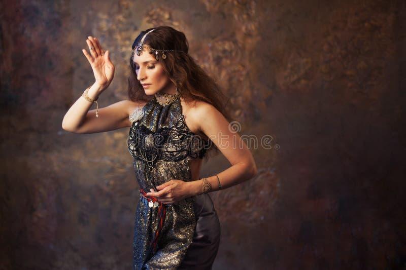 Stammendanser, mooie vrouw in de etnische stijl op een geweven achtergrond stock foto's