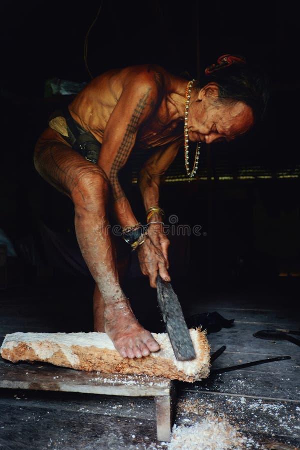 Stammenlid die een boomstam van de sagoboom voor het koken in zijn wildernishuis malen royalty-vrije stock afbeeldingen