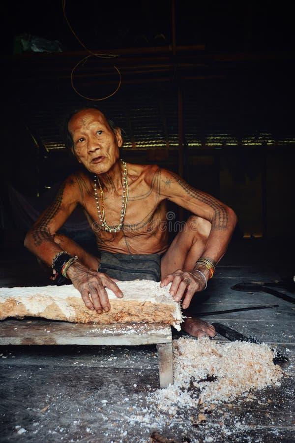 Stammenlid die een boomstam van de sagoboom voor het koken in zijn wildernishuis malen stock afbeelding