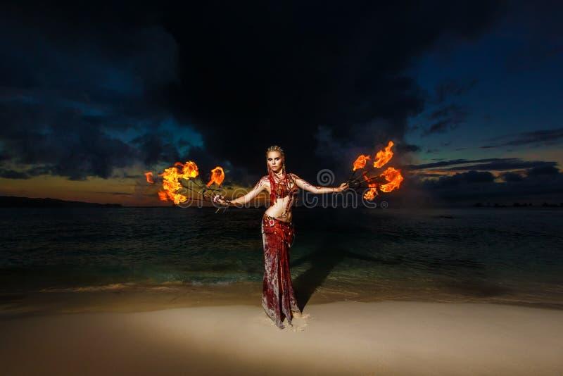 Stammenstijlmeisje op een tropisch strand die met brand bij sunse dansen royalty-vrije stock foto