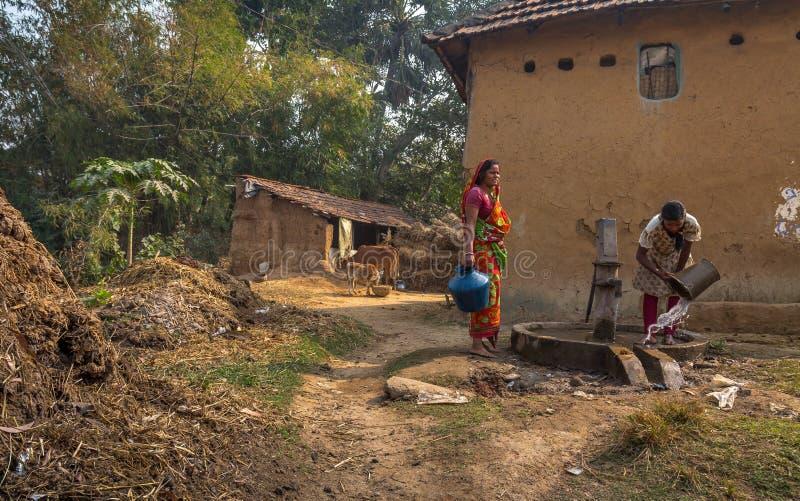 Stammes- Frauen zeichnet Wasser von einem tiefen Rohr gut an einem ländlichen indischen Dorf stockbilder