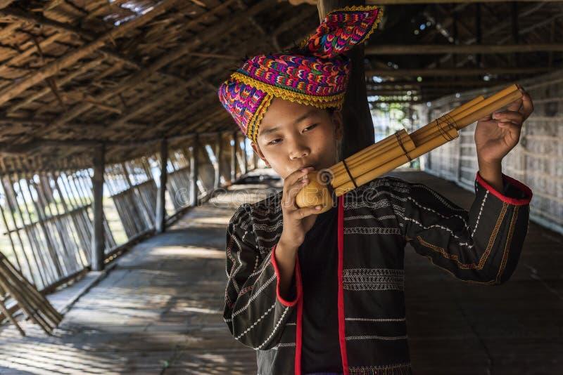 Stammes- Junge Rangus in seinem traditionellen Kostüm, das Sompoton spielt, das von den Bambusrohren gemacht wird, Kudat Malaysia lizenzfreies stockbild