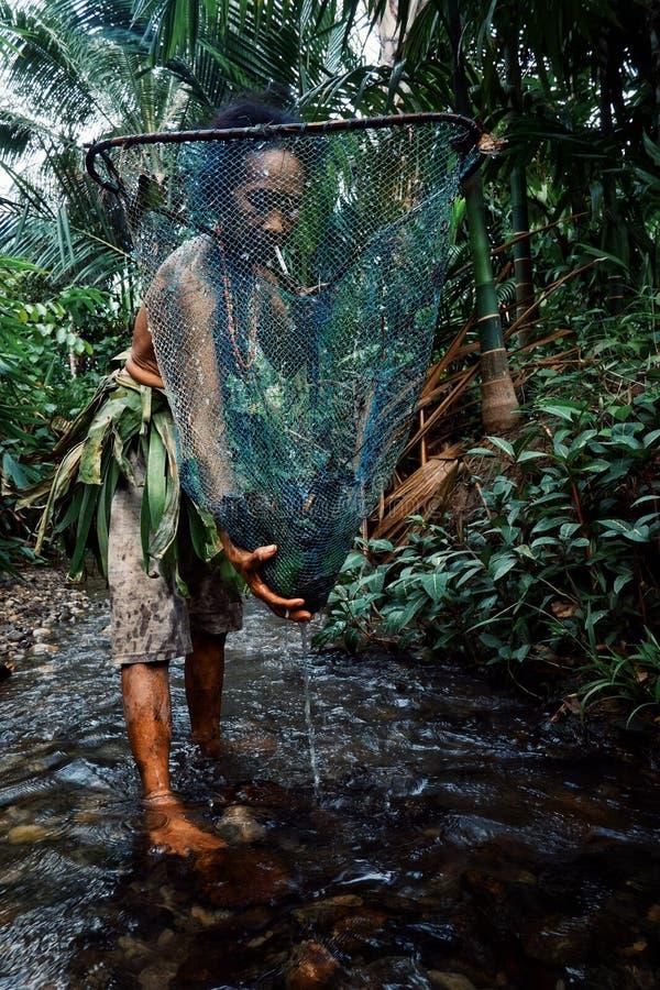 Stammes- Mitgliedsdamenfischen für kleine Fische und Garnelen im Dschungel stre stockfoto
