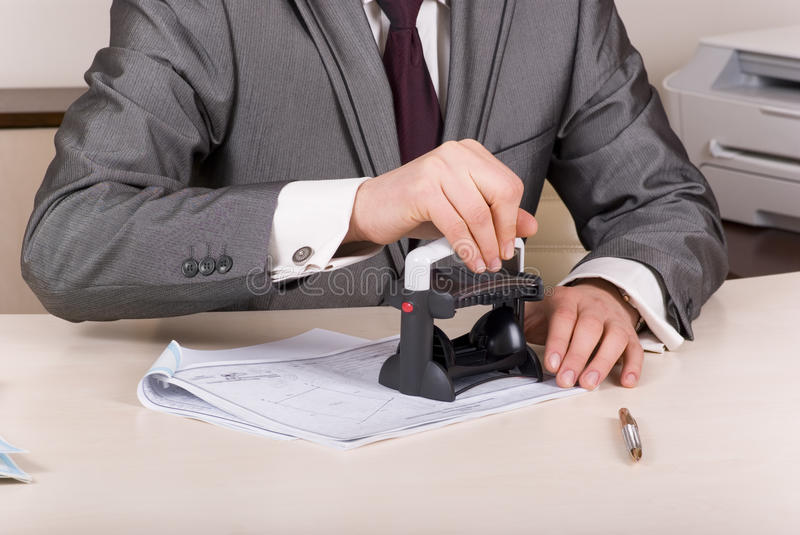 Stamp for imprinting on. A person at a desk using a stamp on documents stock photo