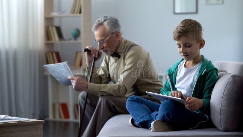 Stampa della lettura del nonno, ragazzo che per mezzo della compressa, generazioni e progresso tecnologico immagini stock libere da diritti