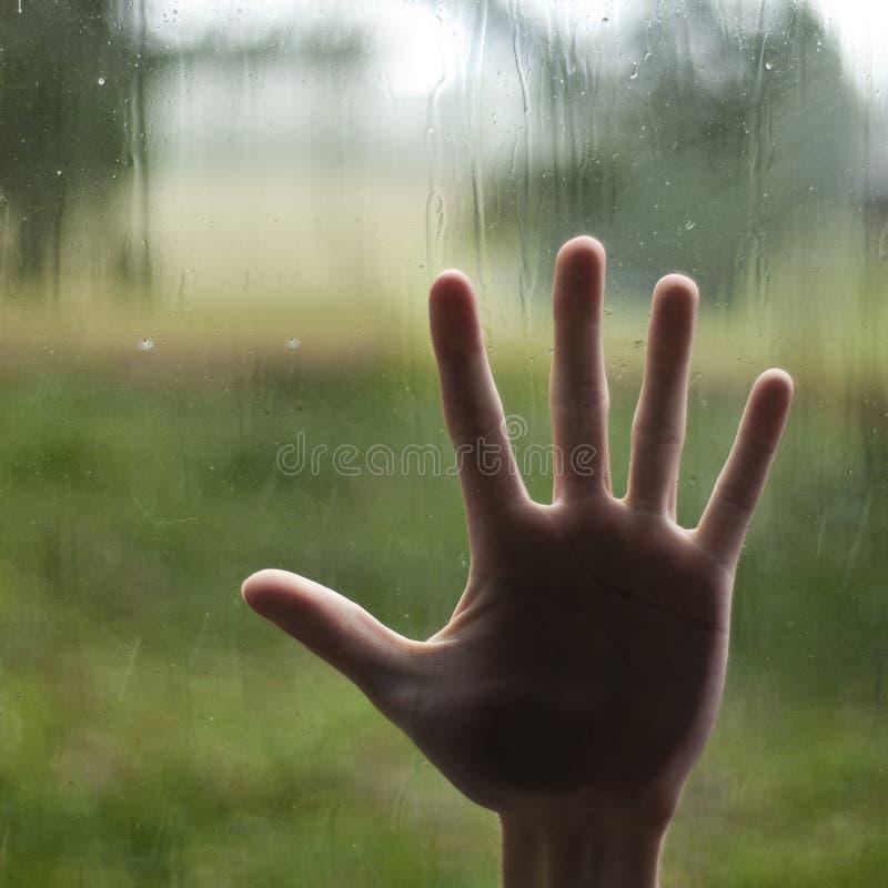 Stampaggio a mano contro la finestra fotografia stock