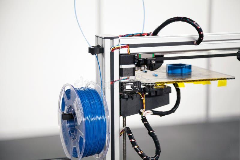 stampante 3d con il primo piano blu della bobina del filamento processo di stampa 3d fotografia stock