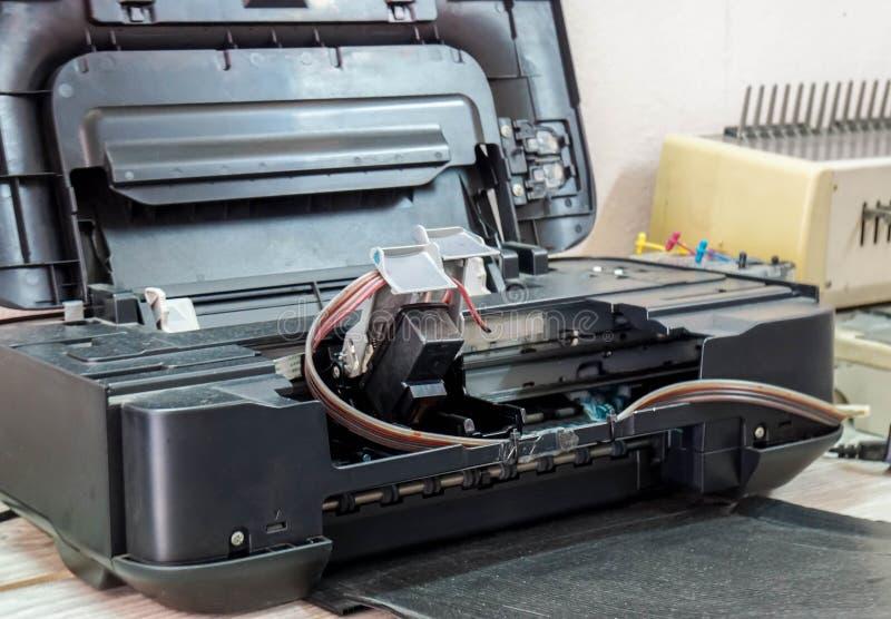 Stampante guastata in corso per la riparazione dal tecnico di manutenzione fotografia stock libera da diritti