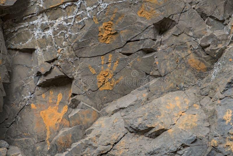 Stampe fangose arancio della mano sulla parete di pietra immagini stock libere da diritti
