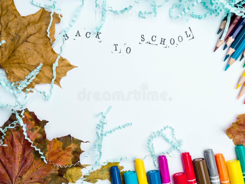 Stamped Inscription back to school with markers, pencils, blue literal paper, and autumn leaves composition mock-up Education. And September concept copy space royalty free stock photography