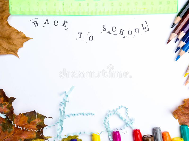 Stamped Inscription. `back to school` with markers, pencils, blue literal paper, green ruler and autumn leaves composition mock-up Education concept copy space stock photography