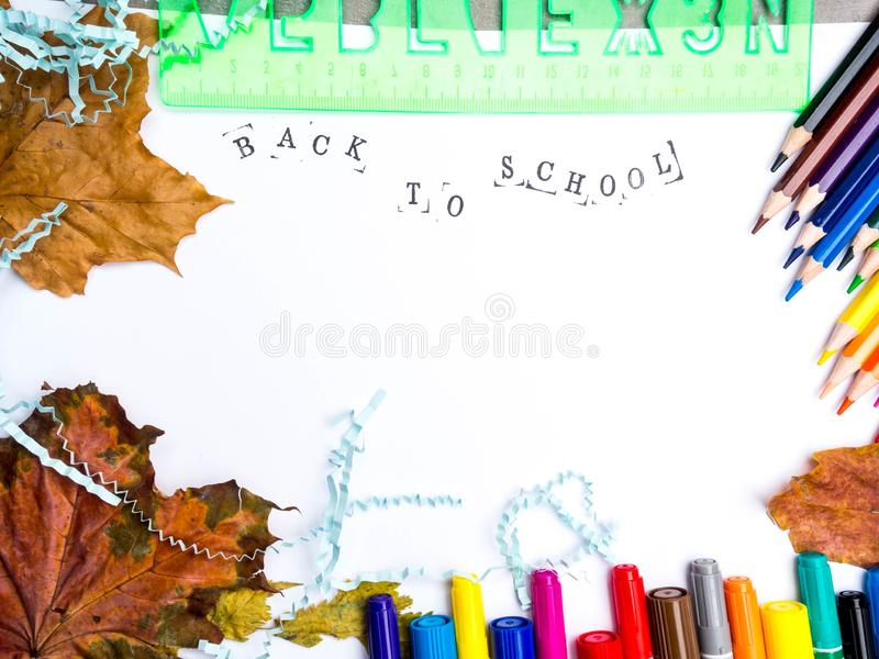 Stamped Inscription back to school with markers, pencils, blue literal paper, green ruler and autumn leaves composition mock-up. Education concept copy space royalty free stock photo