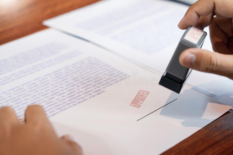 Stamper för färgpulver för hand för affärsmanHand notarius publicu som appoval stämplar skyddsremsan på Approved avtalet för doku arkivfoton