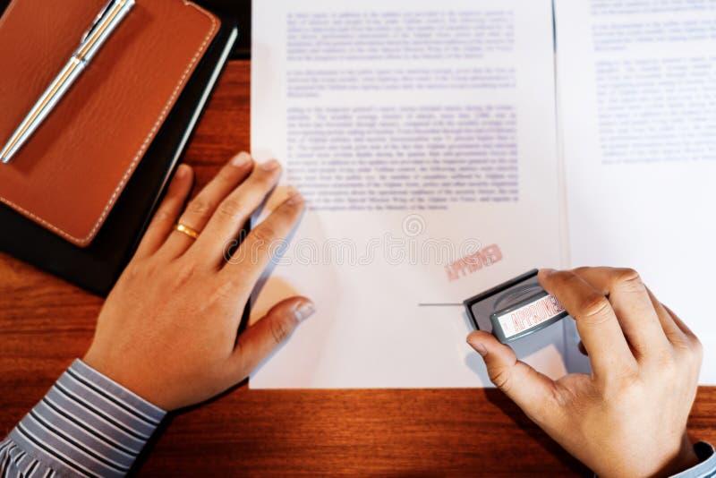 Stamper för färgpulver för hand för affärsmanHand notarius publicu som appoval stämplar skyddsremsan på Approved avtalet för doku royaltyfri foto