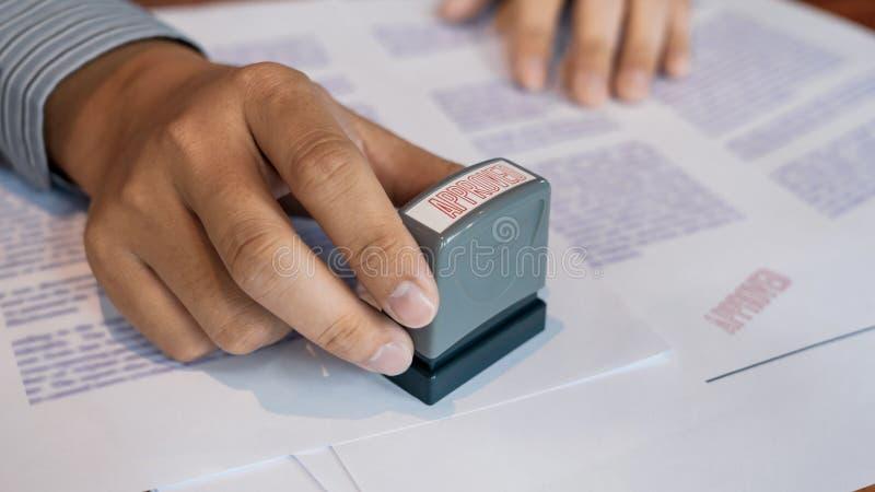 Stamper för färgpulver för hand för affärsmanHand notarius publicu som appoval stämplar skyddsremsan på Approved avtalet för doku arkivbilder