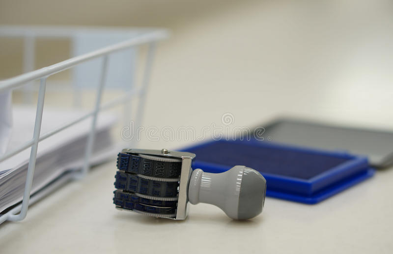 Stamper and ink pad at office. The date stamp placed close to ink pad on desk at office stock photos
