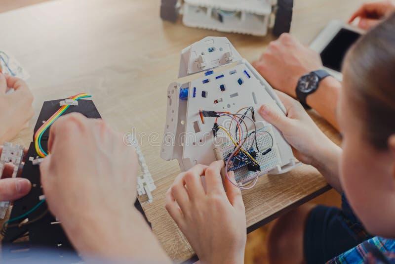 STAMutbildning Ungar som skapar robotar med läraren arkivfoton