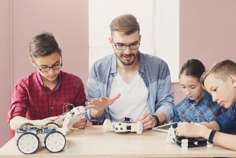 STAMutbildning Ungar som skapar robotar med läraren fotografering för bildbyråer