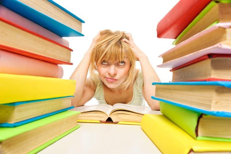 Stanco degli studi, giovane donna sta sedendosi sul suo scrittorio con i libri fotografia stock
