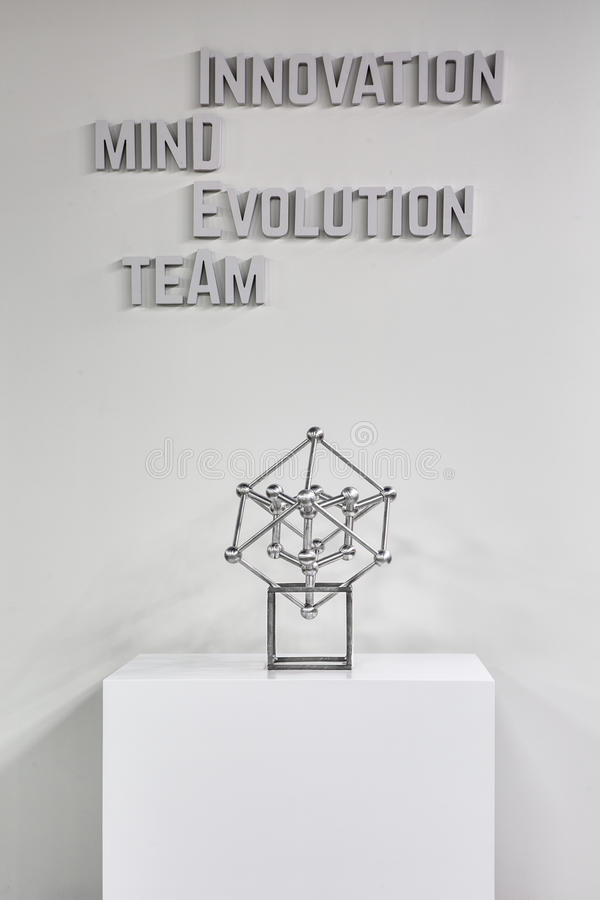 Stand with atom model. White cubic stand with metallic atom model on the white wall background. There is a volumetric gray inscription on the wall. Close-up royalty free stock photography