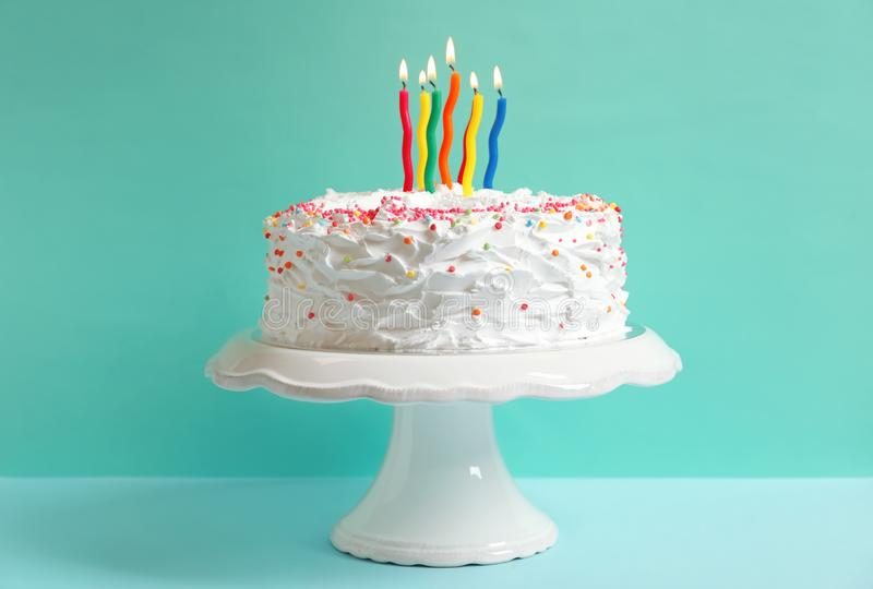 Stand with birthday cake and candles on table. Against color wall royalty free stock image