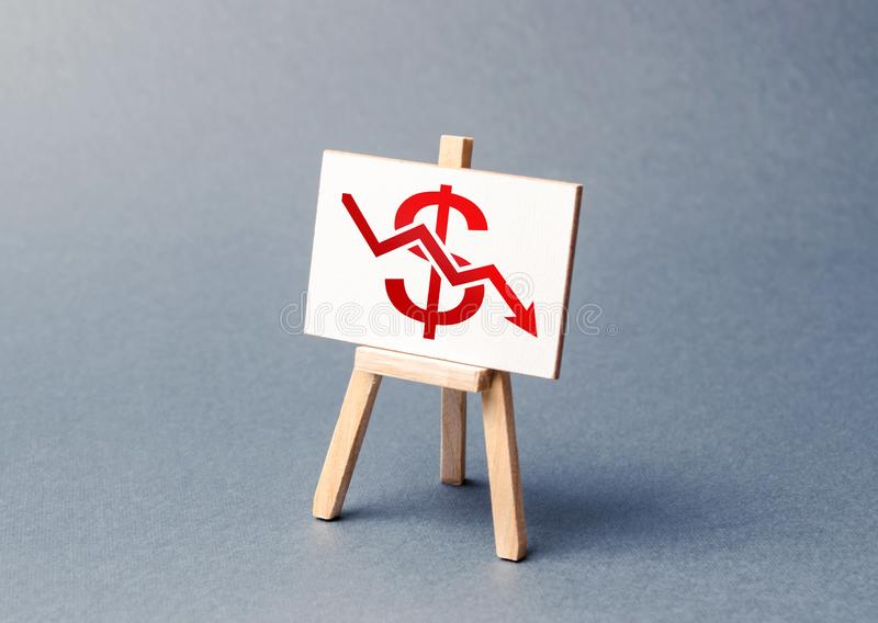 A stand with a canvas and a red dollar arrow down. The concept of falling rates and indicators of the economy or production. Low prices and falling demand royalty free stock images