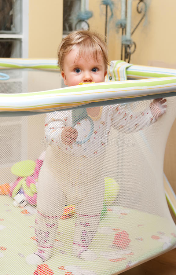Stand de bébé dans le playpen photos libres de droits